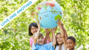 Multi-racial children smile and hold a large globe over their heads together