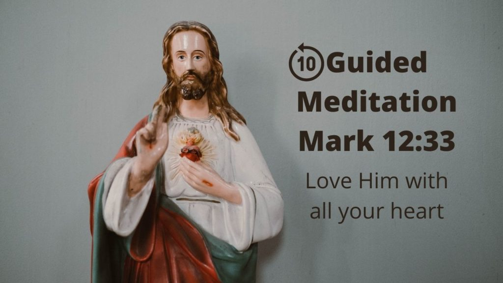 Jesus points two fingers to the heavens and his other hand gestures toward his sacred heart