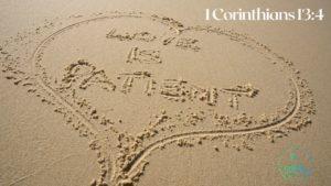 Love is patient written in the sand inside the shape of a heart