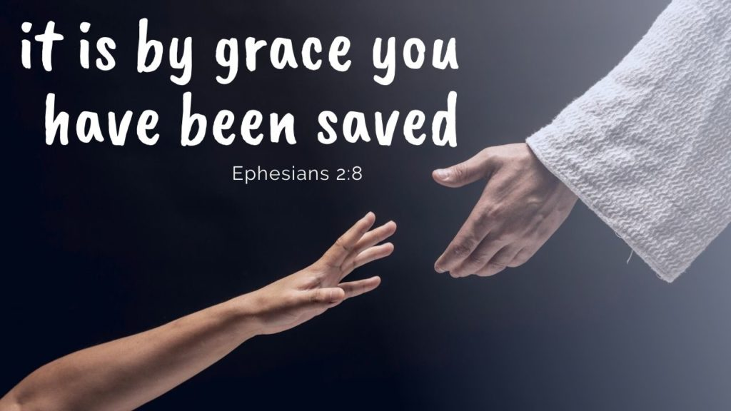 A person's hand reaches up toward Jesus